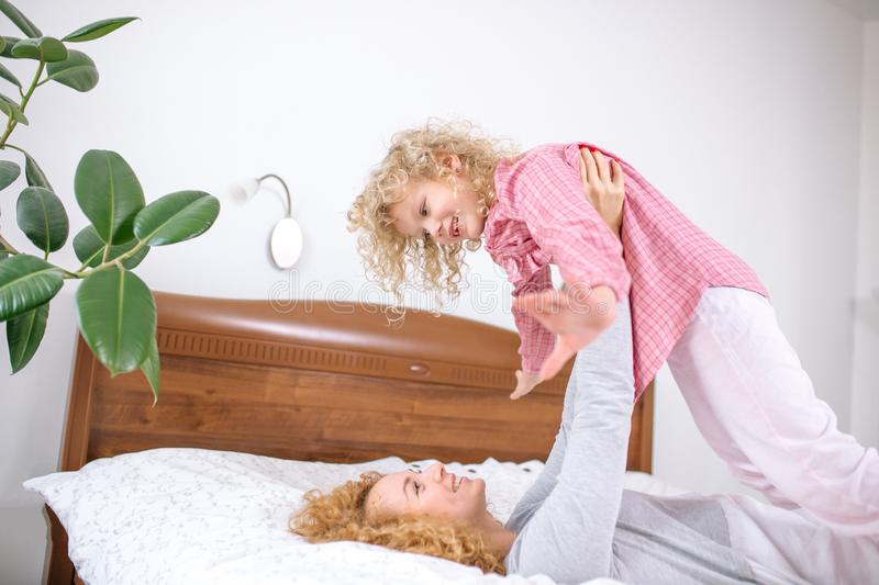 Awesome ginger woman playing with her daughter royalty free stock photo