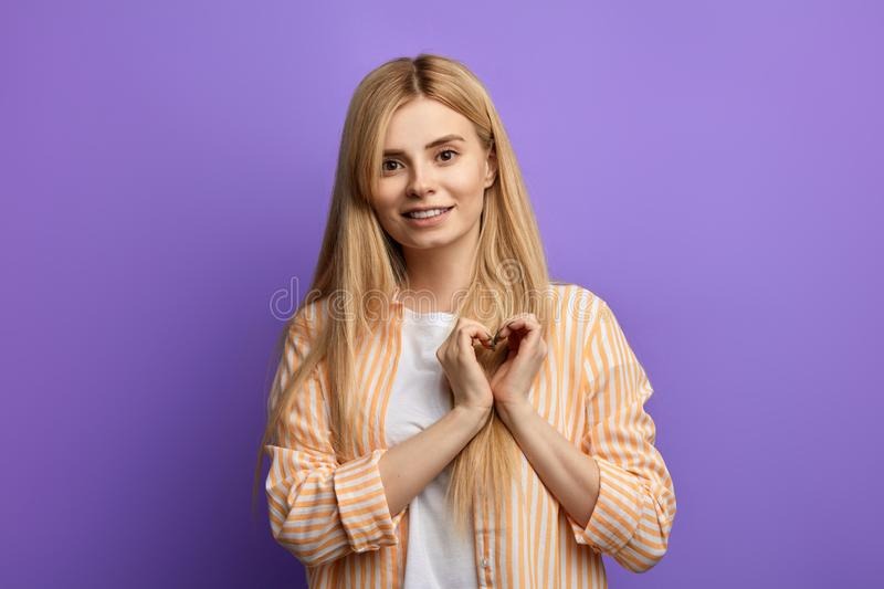 Awesome girl in striped shirt and white T-shirt showing heart with two hands stock image