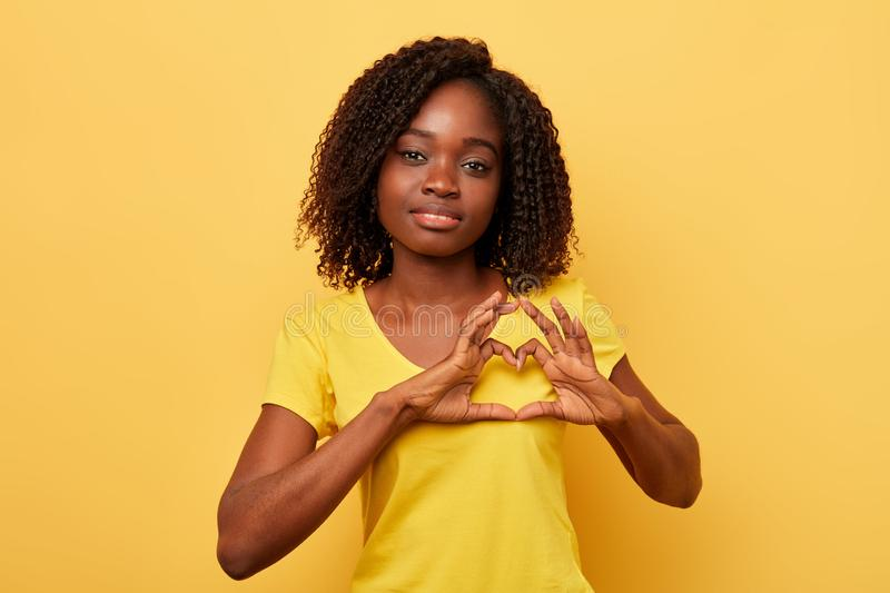 Awesome lovely woman making a heart shape with her hands. And looking at the camera, isolated yellow background. copy space. I love. miss you. studio shot royalty free stock image