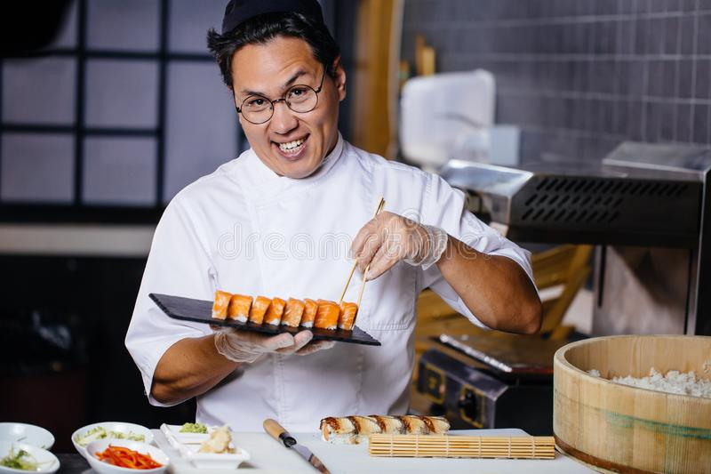 Awesome male making sushi set. For customers. sushi business royalty free stock photos