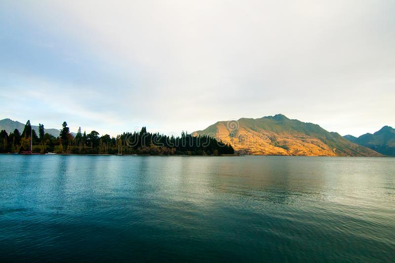 Awesome nature scenery of mountain Cecil Peak and autumn forest above Lake Wakatipu stock image