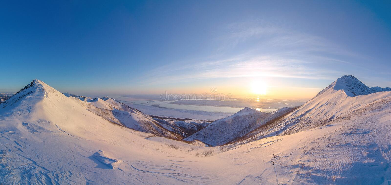 Awesome pano of sunrise above the Ohotskoye sea and Zdanko mountain on Sakhalin island royalty free stock photography