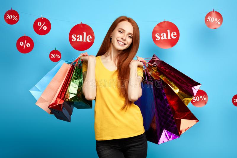 Awesome positive red-haired girl with many packages posing to the camera royalty free stock photography