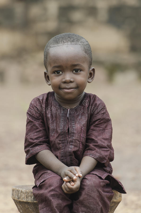 Awesome proud African boy sitting outdoors royalty free stock images