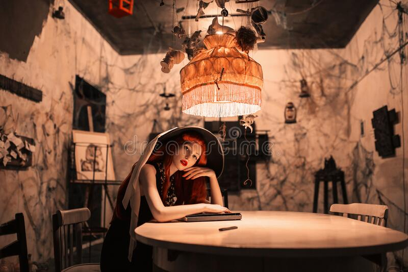 Awesome redhead girl in black retro dress sit at table. Beautiful vintage woman. Awesome lady in retro hat. Vintage writer sit in stock photography