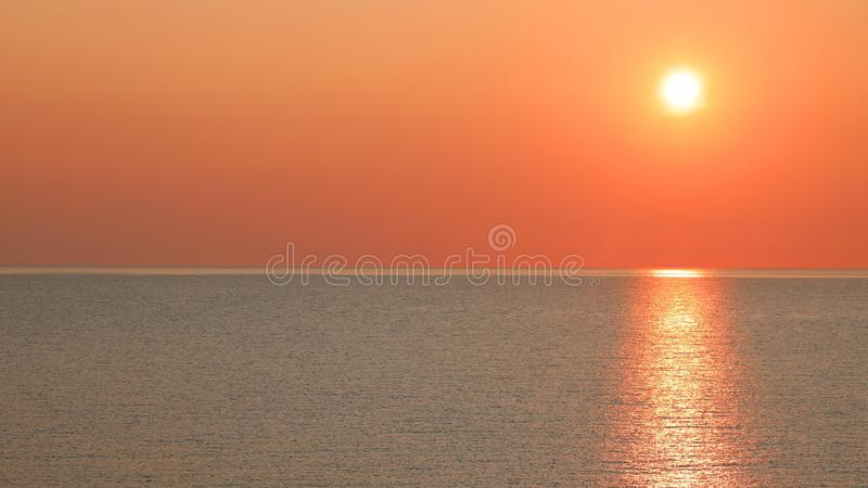 Awesome reflect of the sun at sunset. On the ocean stock photography