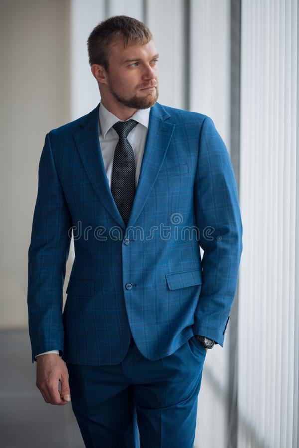 Awesome smart man in fashion suit is looking at the window royalty free stock photography