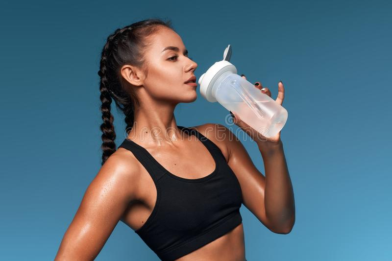 Awesome sportswoman gets pleasure from drinking water from bottle stock image