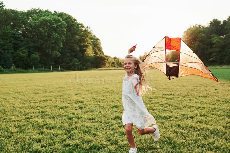 Awesome to be here. Happy girl in white clothes have fun with kite in the field. Beautiful nature royalty free stock photography
