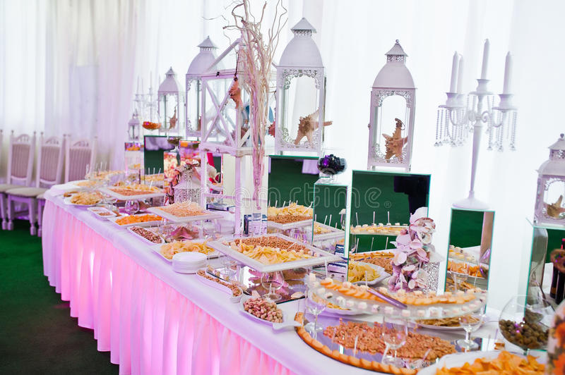 Awesome wedding reception of food and drink. With various pink light, nuts cheese snacks royalty free stock photo