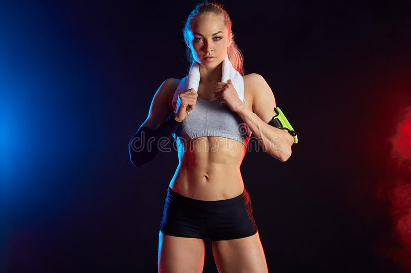 Awesome woman in stylihs sportswear with towel on her shoulder royalty free stock image