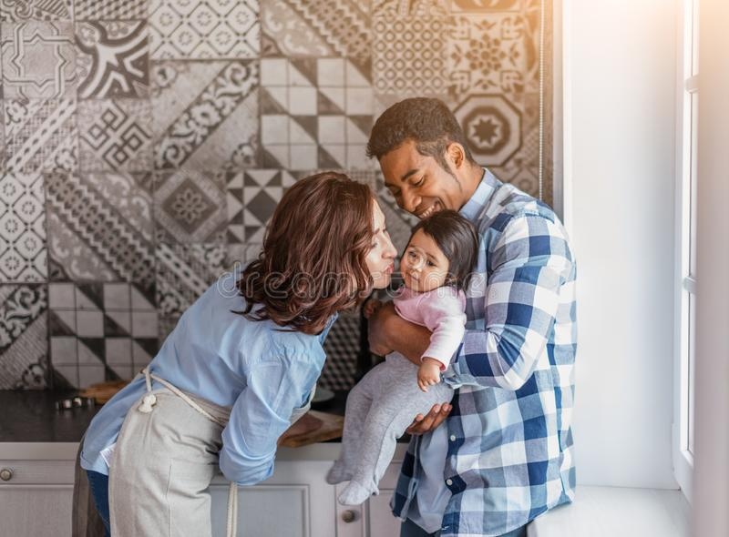 Awesome woman giving a kiss to her baby royalty free stock photography
