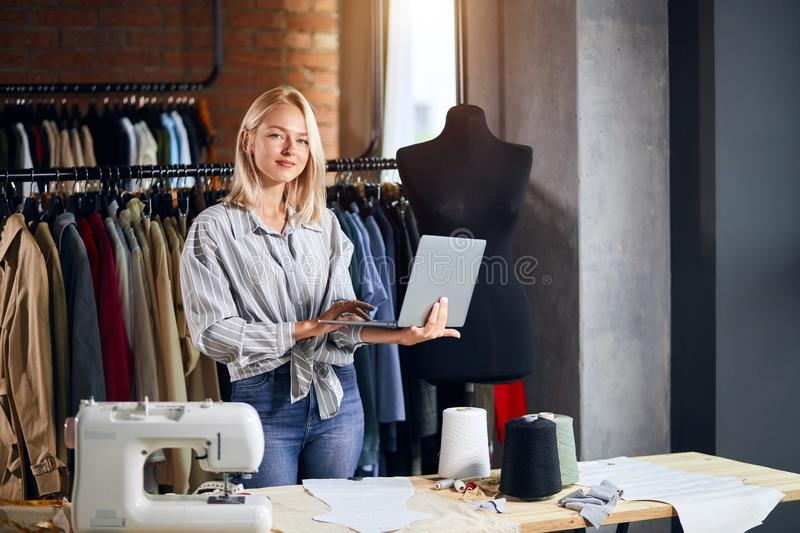 Awesome young female dressmaker holding laptop royalty free stock image