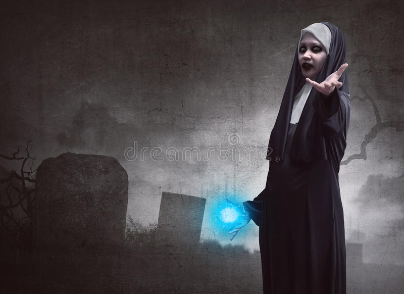 Awful asian woman nun with magic blue power royalty free stock photography