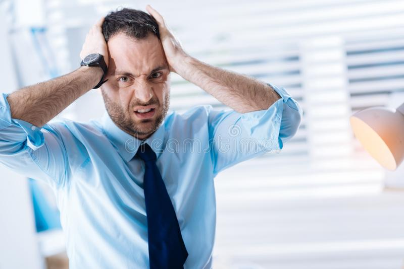 Unhappy bearded man holding his head and expressing his negative feelings stock image