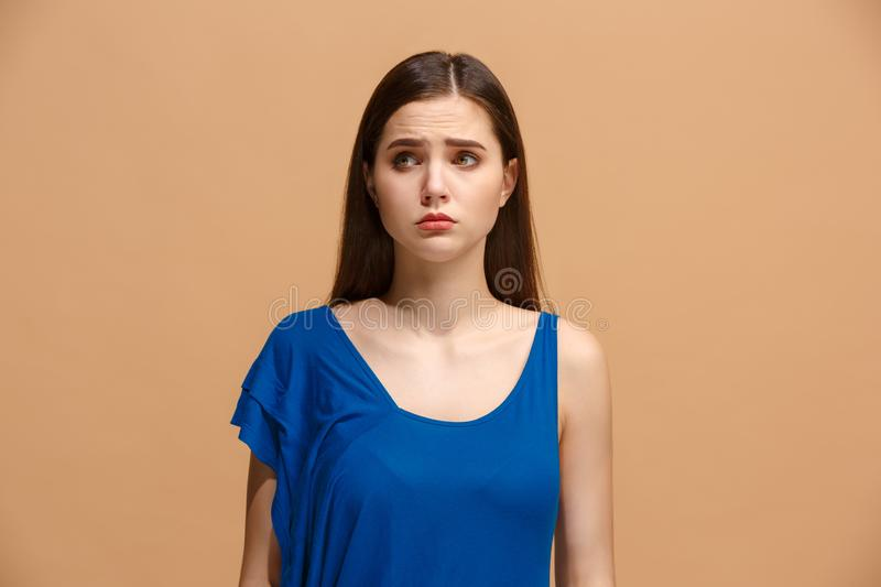 The awkward woman standing and looking at camera against pastel background. The awkward woman is standing and looking at camera on trendy pastel studio stock images