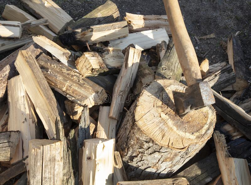The ax cleaver chopped wood and sticks out of the deck stock image