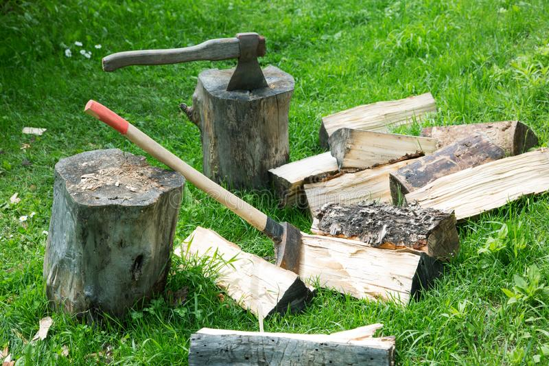 Ax and cleaver on chopped firewood. On a summer day stock image