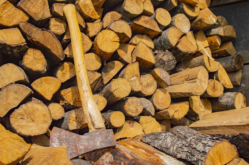 The ax lies on the stacked chopped wood - deforestation royalty free stock photos