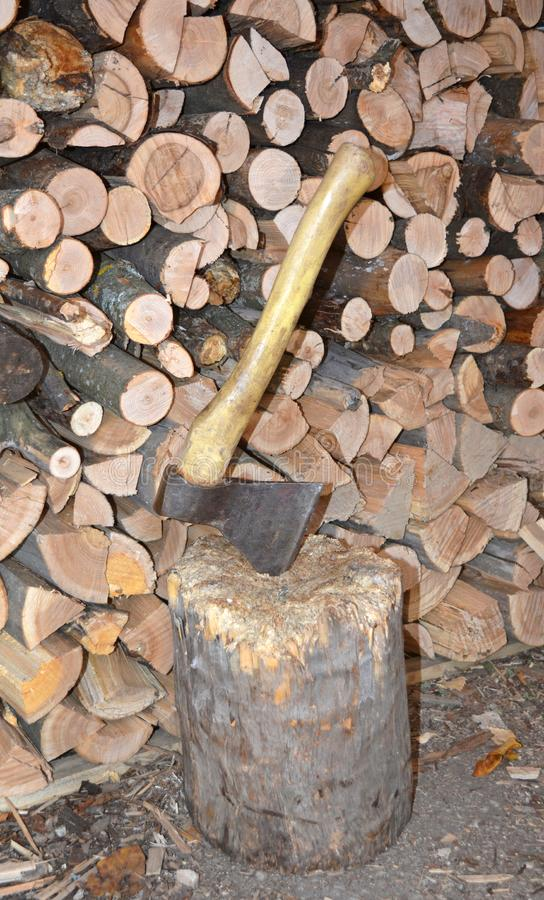 Ax in the log. Woodpile end of tightly packed chopped logs. royalty free stock photo
