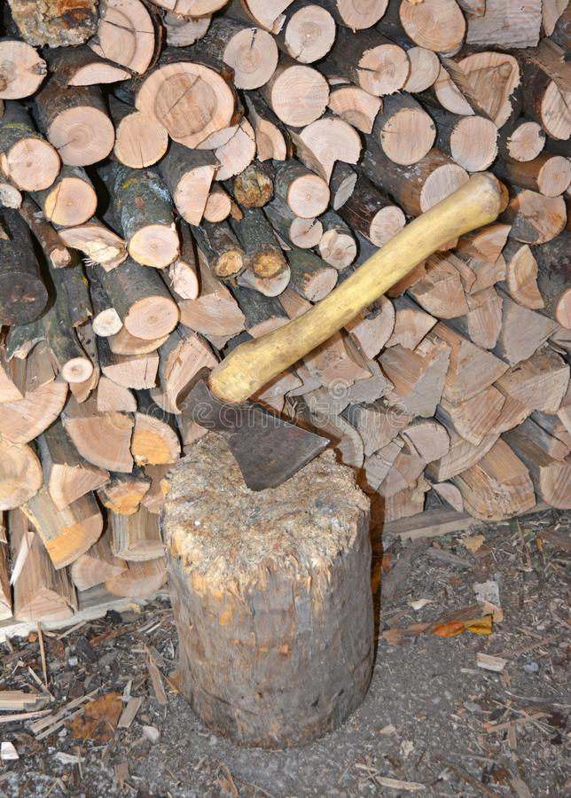 Ax in the log. Woodpile end of tightly packed chopped logs. royalty free stock image