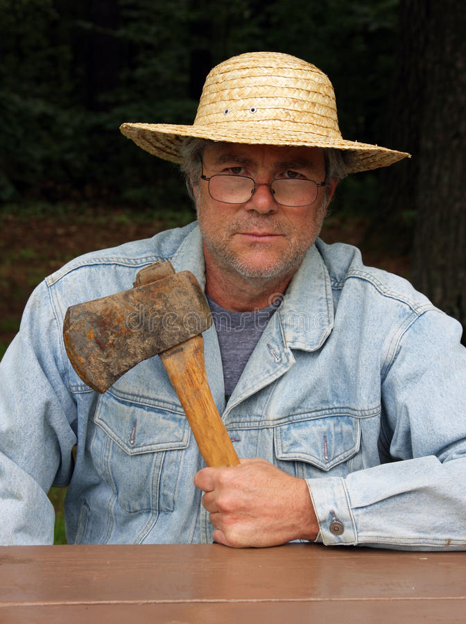 Ax man. Man holding ax wearing jean jacket and straw hat royalty free stock photography