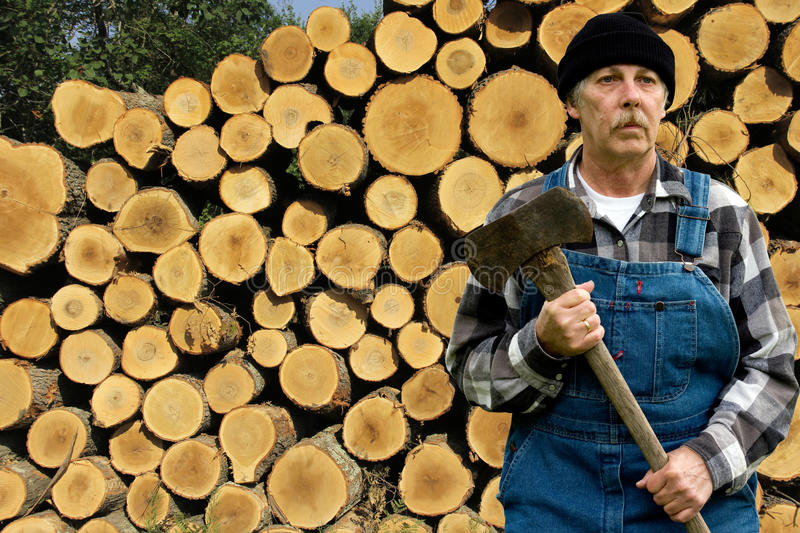Ax man and log pile. Portrait of a man holding an ax with a log pile in the background stock photography