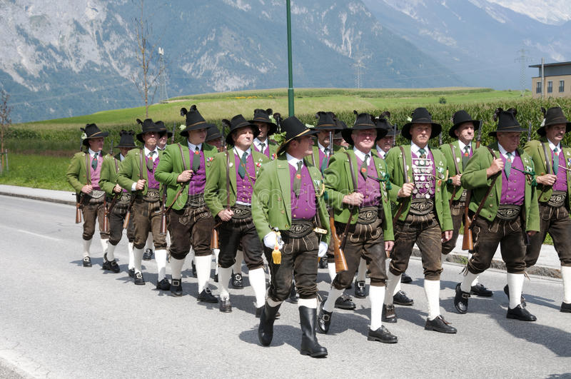 People in costume walking and making music in procession. AXAMS,AUSTRIA - AUGUST 15:Unidentified people making music in procession to the church on Maria royalty free stock photography