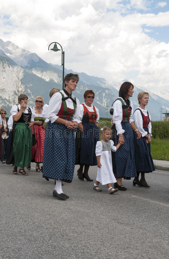 Female and girls walking i traditional dresses in austria procession. AXAMS,AUSTRIA - AUGUST 15:Unidentified peoplewalking in procession to the church on Maria royalty free stock photography