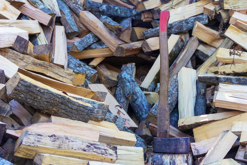 Axe cleaver and a bunch of chopped beech, hornbeam and ash firewood for the stove and fireplace. Closeup stock images