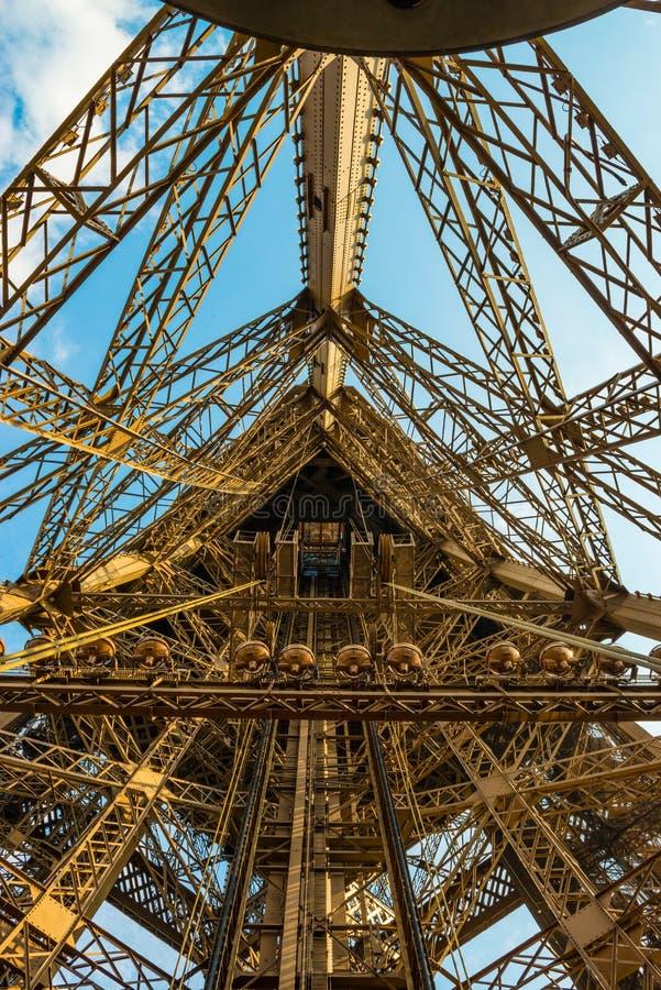 Axe d'ascenseur sur Tour Eiffel dans un tir grand-angulaire montrant les grandes lumières de cuivre photo libre de droits