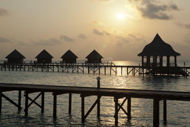 Axe de silhouette au-dessus de l'eau au coucher du soleil maldives photographie stock