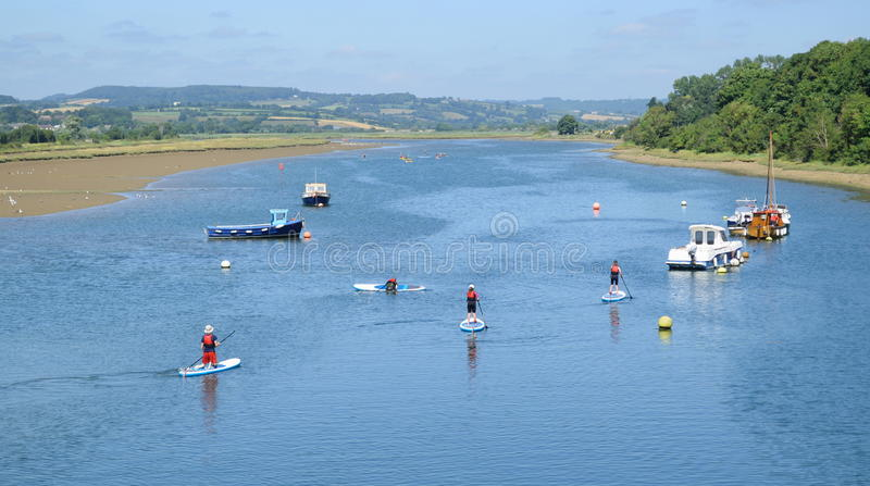 The Axe Estuary. In Seaton during high tide with stand up paddlers royalty free stock photos