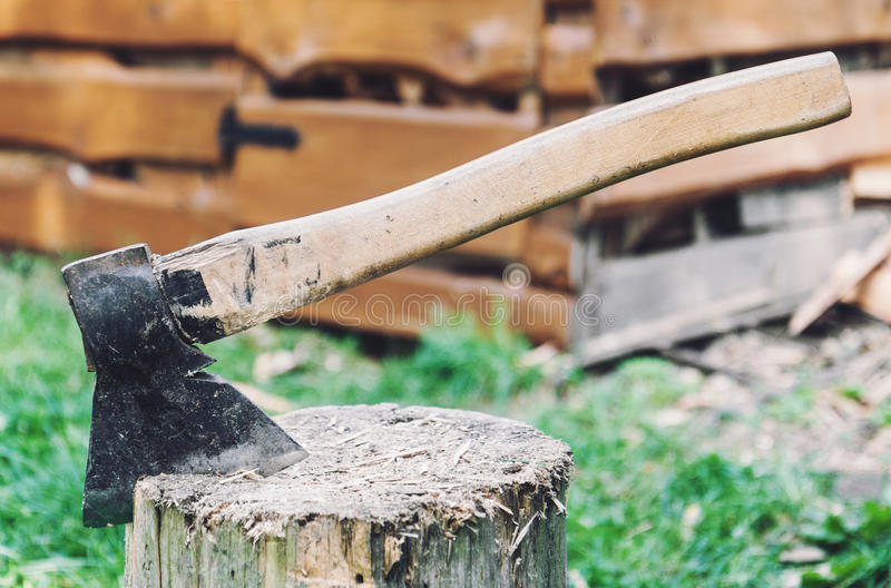 Axe in a log. Closeup of axe in a log in rural background royalty free stock images