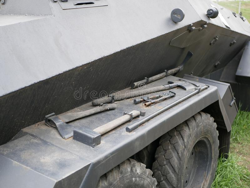 An axe, shovel, wrench, pickaxe, sledgehammer and other tools are attached to a German armoured personnel carrier from world war I. I stock images