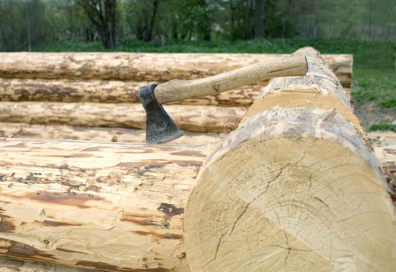 Axe stuck in a log closeup stock photo
