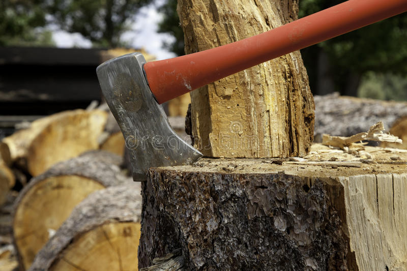 Axe wedged into tree stump royalty free stock photo