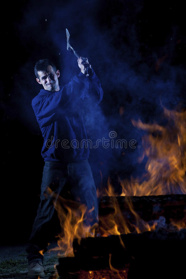 Axe wielding maniac by a fire royalty free stock photo