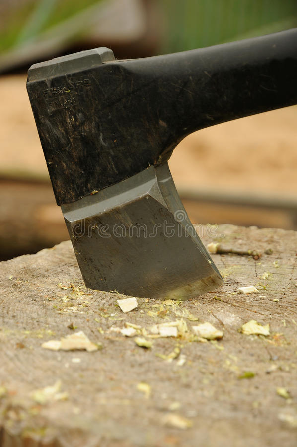 Axe in wooden block. Closeup of sharp axe blade in the wooden block royalty free stock photography