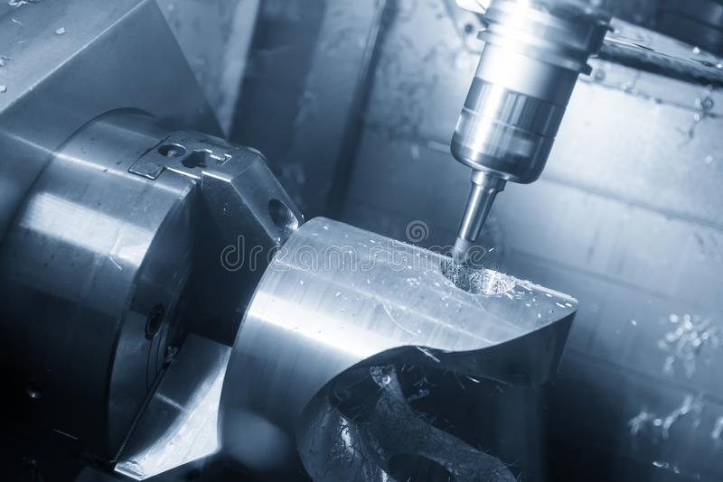 The  5-axis CNC machining center  cutting the automotive part with solid ball end mill. The hi technology manufacturing process of automotive parts stock photography
