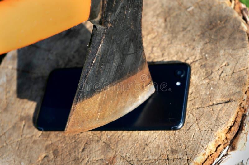 Axt schneidet das Telefon Zerstören Sie Innovation Vandalismustat Smartphone auf dem Stumpf Smartphone nahe der Axt Die Axt im St stockbilder