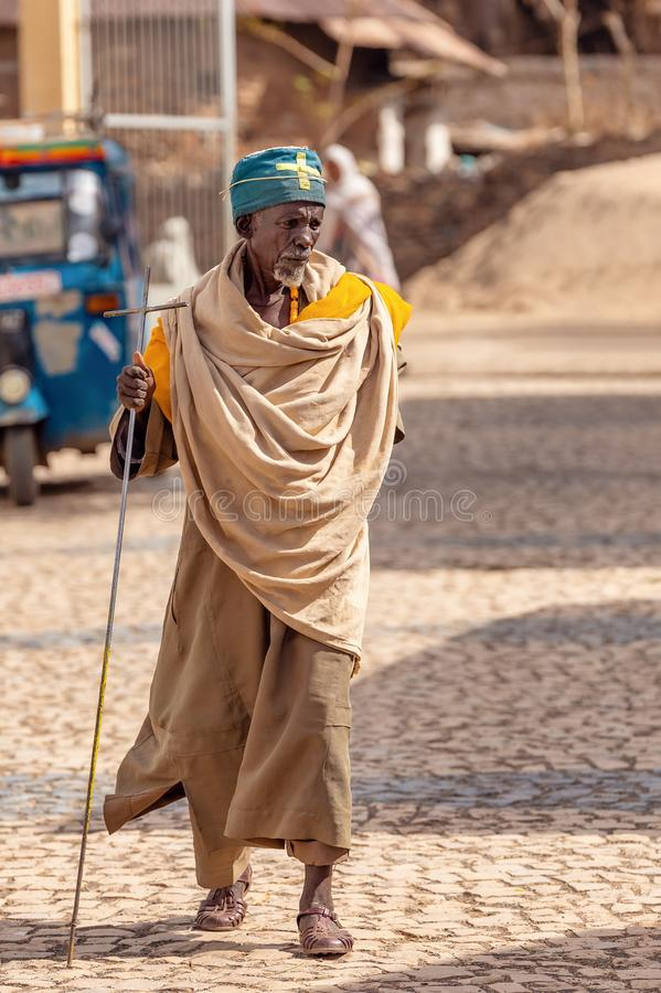 Orthodox monk walk on empty street of Aksum, Ethiopia. AXUM, ETHIOPIA, APRIL 27th.2019: Old man, orthodox monk or priest walk with crutch on empty street of royalty free stock photography