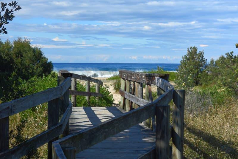 Ay Führen des hölzernen Wegs zu einen Strand mit einer brechenden Welle stockfoto
