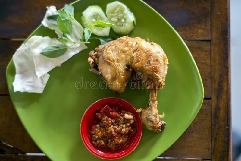 Ayam Penyet (zertrümmertes gebratenes Huhn), ein allgemeines Javaneselebensmittel fand an der Straße von Indonesien lizenzfreie stockbilder