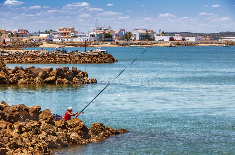A sole fisherman in a red shirt sits on rocks looking across to a quaint fishing village royalty free stock photography