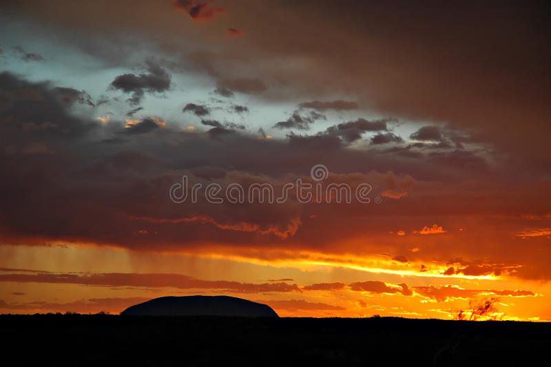 Ayers rock silhouette. Ayers rock during stormy sunset stock photography