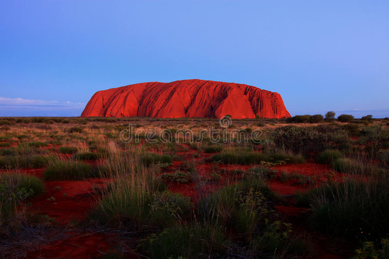 Ayers Rock - Uluru. The impressive Ayers Rock in the middle of the Australian Red Centre a little while after sunset stock photos