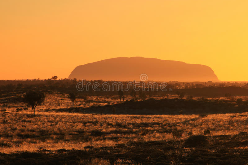 Ayers Rock - Uluru. Remote view of the impressive Ayers Rock in the middle of the Australian Red Centre, shortly after sunrise royalty free stock image
