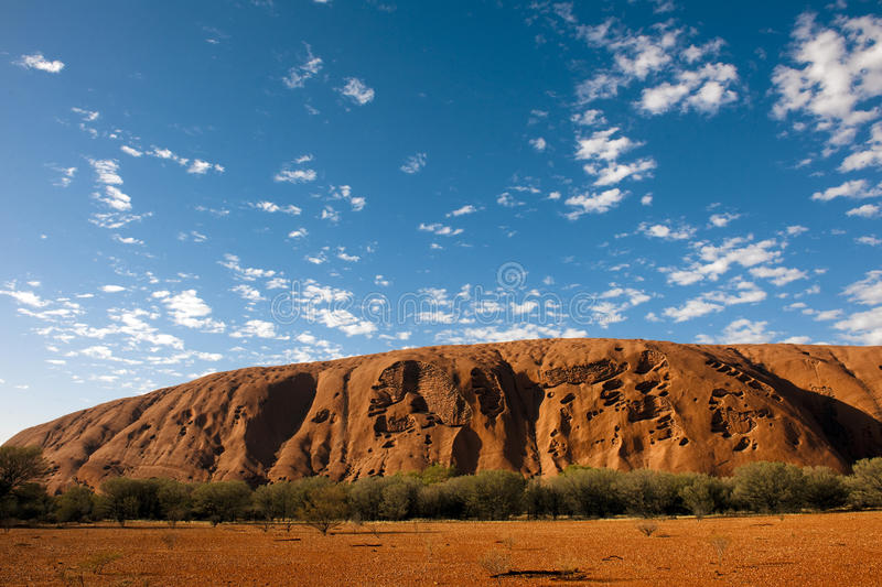 Ayers Rock, Uluru, craggy Part of Tourist Attraction Ayers Rock, Australia. Part of the Ayers Rock in the morning sun with blue sky and clouds stock photography