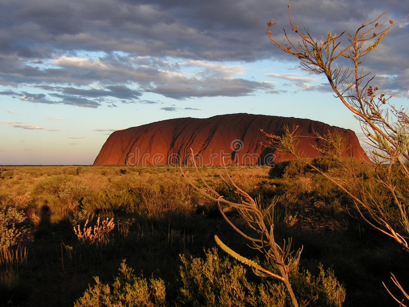 Ayers Rock - Uluru. Ayers Rock (a.k.a. Uluru) in the red centre of Australia. The shadows of some clouds turn the sunset look into something more dramatic stock images
